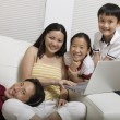 Family on Couch Using Laptop portrait — Stock Photo