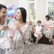 Woman showing gift at baby shower — Stock Photo
