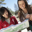 Women with mountain bikes reading map — Stock Photo #33810519