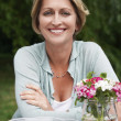 Womsitting at table in garden — Stock Photo #33819985