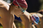 Swimmers on starting blocks — Stock Photo