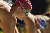 Swimmers on starting blocks — Stock Photo