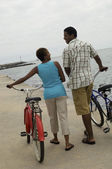 Couple walking with bicycles — Stock Photo