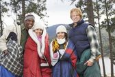 Friends wrapped in blankets by the lake — Stock Photo