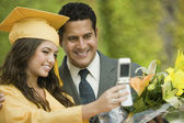 Graduate and father taking picture — Stock Photo
