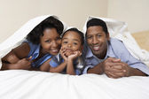 Couple with son lying underneath sheet — Stock Photo