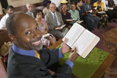 Preacher at altar holding open Bible — Stock Photo