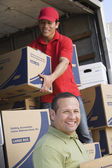 Man with worker unloading delivery van — Stock Photo