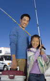Father and daughter holding fishing poles — Stock Photo