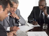 Businessmen at conference table — Stockfoto
