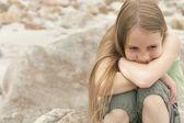 Girl sitting on rock at beach — Stock Photo