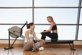 Two women at rowing machine — Stock Photo
