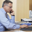 Businessman on call while using laptop — Stock Photo #33821603