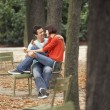 Couple eating snack in park — Stock Photo