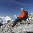 Mountain climber using laptop — Stok fotoğraf