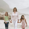 Woman and daughters walking on beach — Stock Photo #33824217