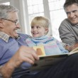 Stock Photo: Grandfather Reading to Granddaughter