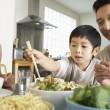 Parents watching son trying to use chopsticks — Stock Photo #33824557