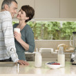 Foto Stock: Smiling couple flirting in kitchen