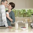 Smiling couple flirting in kitchen — Stock Photo #33824875