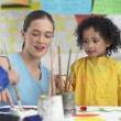 Stock Photo: Teacher and girl painting