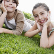 Boy and girl reclining hands on chin — Stock Photo