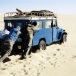 Stockfoto: Men pushing jeep in desert