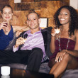 Man with women sitting on couch in bar — Stock Photo #33826435