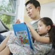 Daughter with picture book beside father — Stock Photo