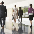 Businesspeople walking in office corridor — Stock Photo #33827503