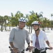 Happy active senior couple with bicycles on tropical beach — Stock Photo