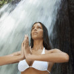 Woman meditating by waterfall — Stock Photo #33828353