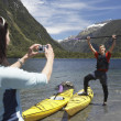 Stock Photo: Womtaking picture of mhoisting oar
