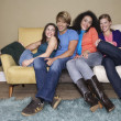 Friends sitting arms around one another on sofa — Stock Photo