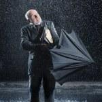 Businessman struggling to open umbrella — Stock Photo #33829531