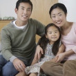 Couple and daughter Posing on Sofa — Stock Photo #33829665