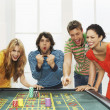 Friends celebrating win on roulette table — Stock Photo #33829797
