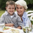 Stock Photo: Grandmother with grandson on lap in garden