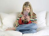Girl playing handheld video game — Stock Photo