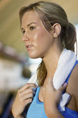 Woman with towel  in gym — Stock Photo