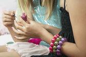 Girl applying nail polish to friends — Stock Photo