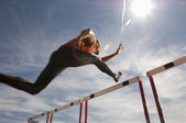 Thlete jumping hurdle — Stock Photo