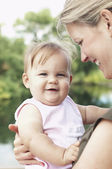 Mother holding daughter by lake — Stock Photo
