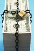 Stack of Dollars secured by padlock — Stock Photo