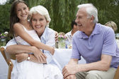 Grandparents with granddaughter in garden — Stock Photo