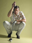 Golfer squatting and squinting — Stock Photo