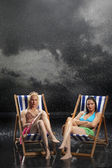 Sunbathers sitting in sunloungers — Stock Photo
