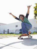 Man with arms raised on skateboard — Stock Photo