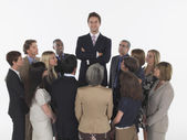 Businesspeople Staring at Tall Man — Stock Photo