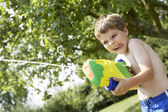 Boy shooting with water pistol — Stock Photo